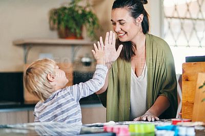 Buy stock photo Shot of an adorable little boy giving his mother a high five while baking together at home