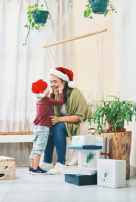 Buy stock photo Shot of a young woman spending quality time with her adorable son at Christmas