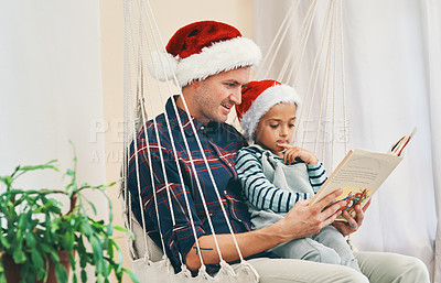 Buy stock photo Shot of a young man reading a book with his adorable son at Christmas