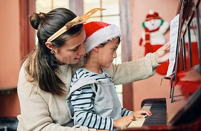 Buy stock photo Shot of an adorable little boy playing the piano with his mother at Christmas