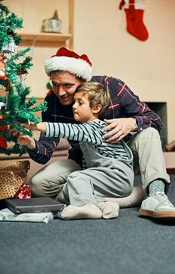 Buy stock photo Shot of an adorable little boy sitting next to the Christmas tree with his father