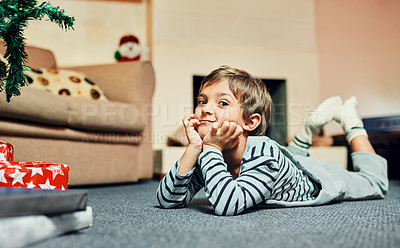 Buy stock photo Shot of an adorable little boy lying down next to the Christmas tree at home