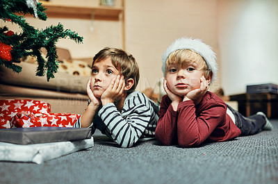 Buy stock photo Shot of two adorable little boys lying down next to the Christmas tree at home