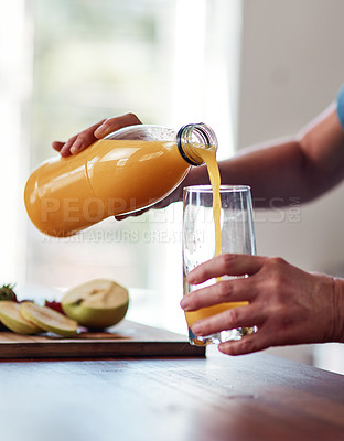 Buy stock photo Cropped shot of an unrecognizable senior woman pouring herself a glass of orange juice while preparing breakfast in the kitchen
