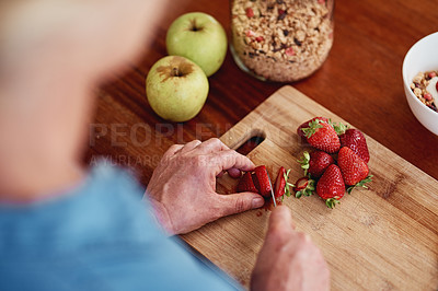 Buy stock photo High angle shot of an unrecognizable senior woman chopping up strawberries and other fruit while preparing breakfast in the kitchen