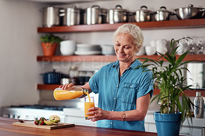 Buy stock photo Cropped shot of an attractive senior woman pouring herself a glass of orange juice while preparing breakfast in the kitchen