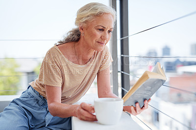 Buy stock photo Cropped shot of an attractive senior woman enjoying a cup of coffee while reading a book outside on her balcony at home