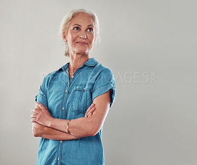 Buy stock photo Cropped shot of an attractive senior woman looking contemplative while standing with her arms folded against a grey background