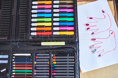 Buy stock photo Still life shot of a set of colored pencils on a table next to a hand drawing indoors