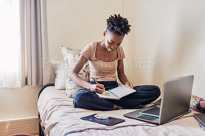 Buy stock photo Shot of an attractive young female university student painting in a notebook in her room