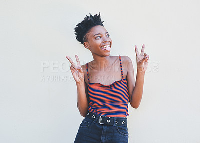 Buy stock photo Cropped shot of an attractive young female university student showing the peace sign while standing against a grey background