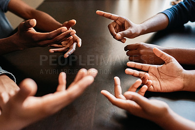 Buy stock photo Closeup of a group of unrecognizable people gesturing with their hands in a circles while being seated at a table