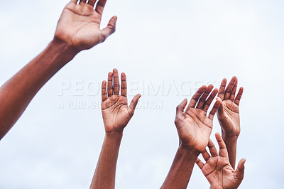 Buy stock photo Cropped shot of a group of unrecognizable people holding their hands in the air outside during the day