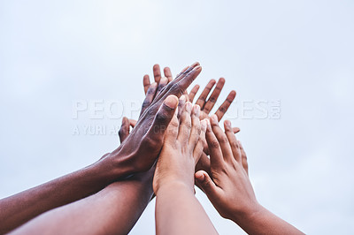 Buy stock photo Cropped shot of a group of unrecognizable people giving each other a high five in the air outside during the day