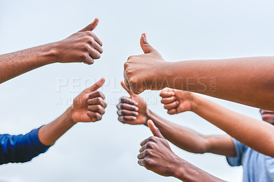 Buy stock photo Cropped shot of a group of unrecognizable people showing thumbs up to each other outside during the day