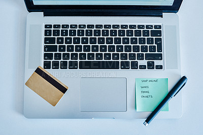 Buy stock photo Cropped shot of a pen and notepad resting with a credit card on top of a laptop inside during the day