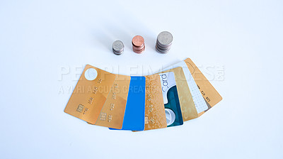 Buy stock photo High angle shot of a collection of credit cards placed next to stacks of coins on top of a white surface inside during the day