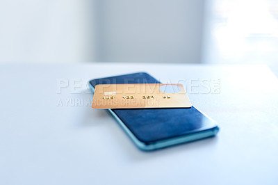 Buy stock photo Closeup of a credit card placed on top of a cellphone while both rest on top of a countertop