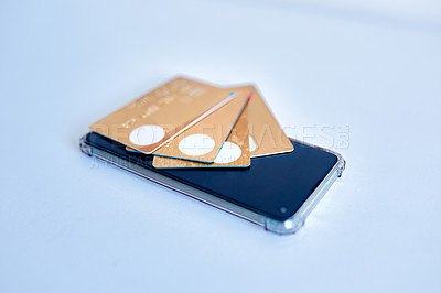 Buy stock photo Closeup of a collection of credit cards placed on top of a cellphone while both rest on top of a white surface
