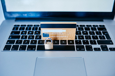 Buy stock photo Closeup of a credit card placed next to a lock while both rest on top of a laptop inside during the day