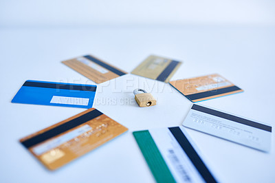 Buy stock photo Closeup of a collection of credit cards placed in a circle with a lock in the middle on top of a white surface