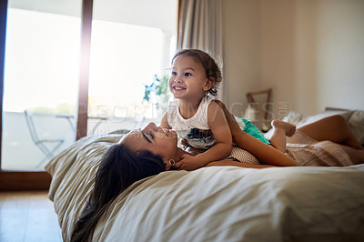 Buy stock photo Shot of an attractive young woman and her young son playing on a bed at home
