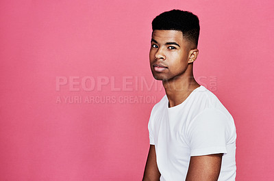 Buy stock photo Cropped portrait of a handsome young man standing alone against a pink background in the studio