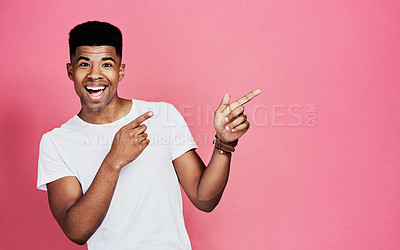 Buy stock photo Cropped portrait of a handsome young man standing and making a hand gesture against a pink background in the studio