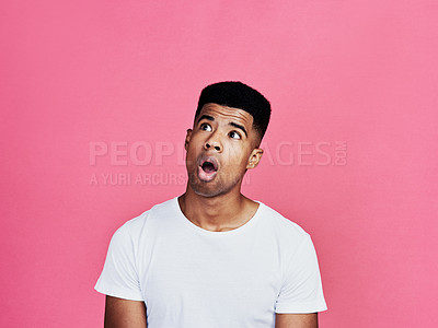Buy stock photo Cropped shot of a handsome young man standing alone and looking shocked against a pink background in the studio