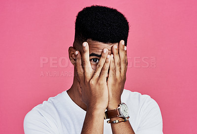 Buy stock photo Cropped portrait of a handsome young man standing alone and covering his face with his hands against a pink background