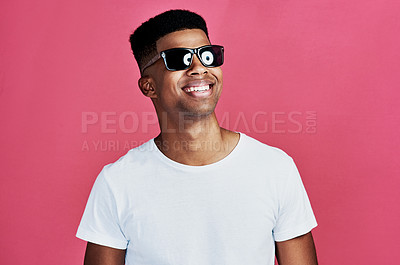 Buy stock photo Cropped shot of a handsome young man standing alone and wearing sunglasses against a pink background in the studio