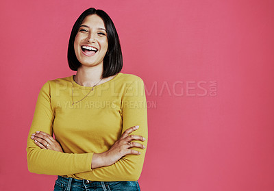 Buy stock photo Cropped portrait of an attractive young woman standing alone with her arms folded against a pink background in the studio