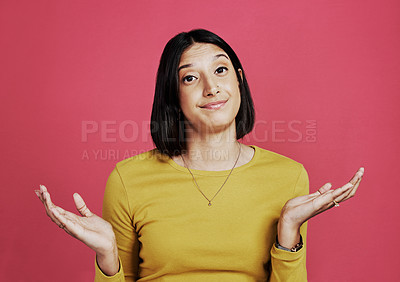 Buy stock photo Cropped portrait of an attractive young woman shrugging and looking confused while standing against a pink studio background alone