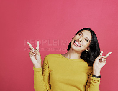 Buy stock photo Cropped portrait of an attractive young woman standing alone and making a peace sign hand gesture against a pink background