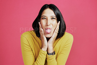 Buy stock photo Cropped portrait of an attractive young woman standing alone and pulling a face against a pink background in the studio
