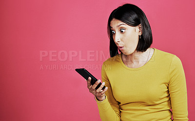 Buy stock photo Cropped shot of an attractive young woman standing alone and looking shocked while using her cellphone against a pink background