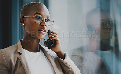 Buy stock photo Shot of a young businesswoman talking on a cellphone while standing at a window in an office