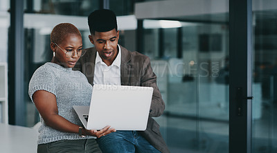 Buy stock photo Shot of two businesspeople using a laptop together in an office