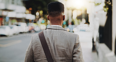 Buy stock photo Rearview shot of a young businessman walking outdoors in the city
