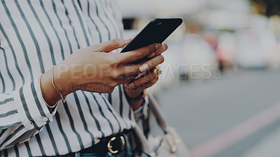 Buy stock photo Cropped shot of an unrecognizable businesswoman using her cellphone while outdoors in the city