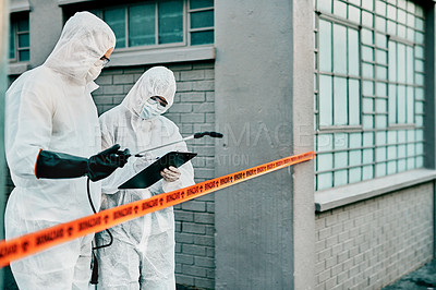 Buy stock photo Shot of two healthcare workers wearing hazmat suits working together during an outbreak in the city