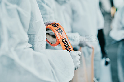 Buy stock photo Shot of a healthcare worker cordoning off an urban area with barrier tape during an outbreak