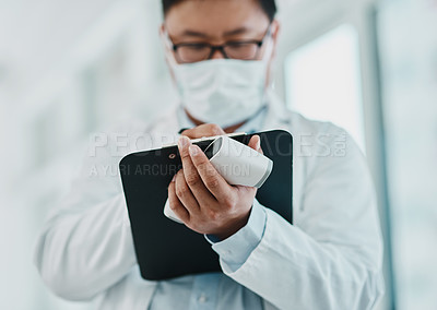 Buy stock photo Shot of a doctor holding an infrared thermometer and writing notes during an outbreak