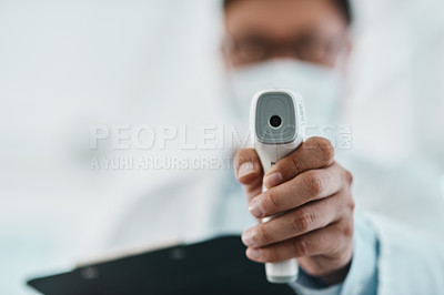 Buy stock photo Shot of a doctor using an infrared thermometer during an outbreak