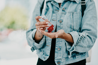Buy stock photo Cropped shot of a woman disinfecting herself with hand sanitiser