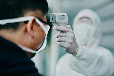 Buy stock photo Shot of a young man getting her temperature taken with an infrared thermometer by a healthcare worker during an outbreak