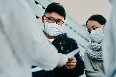 Buy stock photo Shot of a young man talking to a healthcare worker in a hazmat suit during an outbreak
