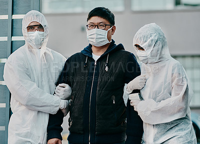 Buy stock photo Shot of a young man getting taken away by healthcare workers in hazmat suits during an outbreak
