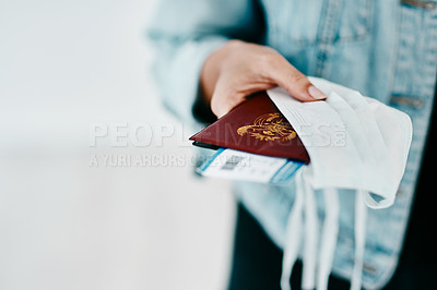 Buy stock photo Cropped shot of a woman holding her passport, mask and boarding pass in an airport