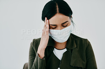 Buy stock photo Shot of a young woman experiencing a headache and wearing a mask against a studio background